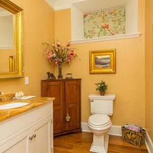 Foto di un bagno di servizio chic con lavabo sottopiano, consolle stile comò, top in onice, WC monopezzo e pavimento in legno massello medio