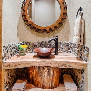 ヒューストンの大きいラスティックスタイルのおしゃれなトイレ・洗面所 (ベッセル式洗面器、オープンシェルフ、中間色木目調キャビネット、木製洗面台、ベージュのタイル、石タイル、ベージュの壁、ライムストーンの床、ベージュのカウンター) の写真