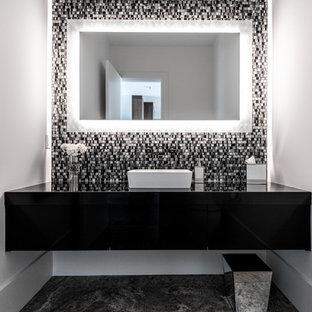 Foto di un bagno di servizio design con ante lisce, ante nere, pistrelle in bianco e nero, piastrelle a mosaico, pareti bianche, lavabo a bacinella, pavimento multicolore e top nero