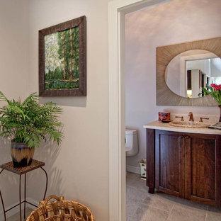 Foto di un bagno di servizio tropicale di medie dimensioni con ante con riquadro incassato, ante in legno bruno, WC monopezzo, pareti beige, pavimento in travertino, lavabo da incasso e top in quarzo composito