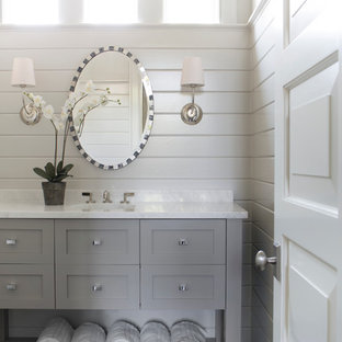 Cette image montre un WC et toilettes marin avec un lavabo encastré, des portes de placard grises, un mur blanc, un sol en bois foncé, un placard à porte shaker et un plan de toilette blanc.