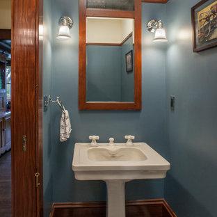 Cette image montre un WC et toilettes craftsman avec un lavabo de ferme, un mur bleu et un sol en carrelage de céramique.