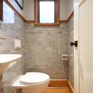 Foto de aseo de estilo americano, pequeño, con sanitario de pared, baldosas y/o azulejos grises, baldosas y/o azulejos de cemento, paredes grises, suelo de madera en tonos medios y lavabo suspendido
