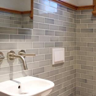 Modelo de aseo de estilo americano, pequeño, con sanitario de pared, baldosas y/o azulejos grises, baldosas y/o azulejos de cemento, paredes grises, suelo de madera en tonos medios y lavabo suspendido