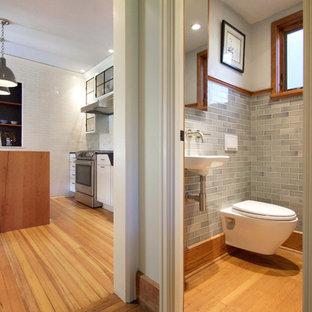 Imagen de aseo de estilo americano, pequeño, con sanitario de pared, baldosas y/o azulejos grises, baldosas y/o azulejos de cemento, paredes grises, suelo de madera en tonos medios y lavabo suspendido