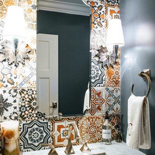 Cette image montre un grand WC et toilettes traditionnel avec un carrelage multicolore, des carreaux de céramique, un mur bleu, un sol en bois brun, un lavabo posé et un plan de toilette en granite.