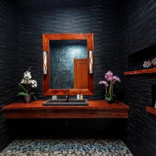 Esempio di un bagno di servizio stile americano di medie dimensioni con piastrelle nere, pareti nere, pavimento con piastrelle di ciottoli, lavabo da incasso, pavimento grigio e top marrone