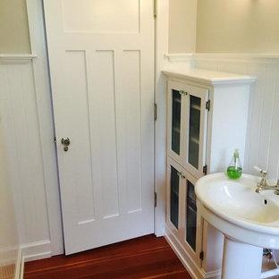 Ejemplo de aseo de estilo americano, de tamaño medio, con armarios tipo vitrina, puertas de armario blancas, paredes blancas, suelo de madera oscura y lavabo con pedestal