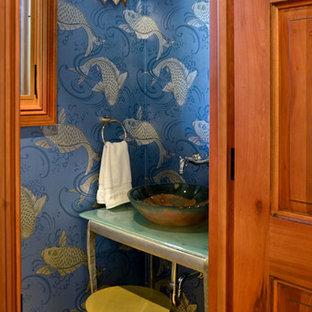 Diseño de aseo mediterráneo, pequeño, con armarios abiertos, sanitario de dos piezas, baldosas y/o azulejos azules, paredes azules, suelo de piedra caliza, lavabo sobreencimera, encimera de vidrio y suelo beige