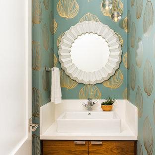 На фото: туалет в современном стиле с плоскими фасадами, фасадами цвета дерева среднего тона, синими стенами, настольной раковиной, коричневым полом и белой столешницей