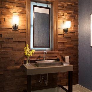 シカゴの中くらいのビーチスタイルのおしゃれなトイレ・洗面所 (コンクリートの洗面台、ライムストーンの床、ベッセル式洗面器、茶色いタイル、青い壁) の写真