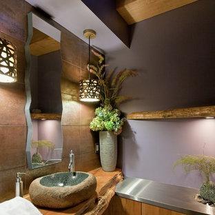 Modern inredning av ett brun brunt toalett, med ett fristående handfat, släta luckor, skåp i mellenmörkt trä, bänkskiva i rostfritt stål, brun kakel, porslinskakel och lila väggar