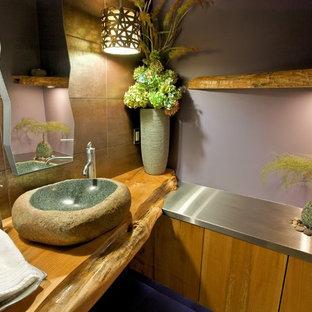 Cette photo montre un grand WC et toilettes rétro avec une vasque, un placard à porte plane, des portes de placard en bois brun, un plan de toilette en acier inoxydable, des carreaux de porcelaine et un carrelage marron.