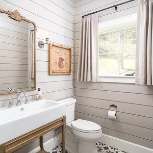 Стильный дизайн: туалет в стиле кантри с открытыми фасадами, фасадами цвета дерева среднего тона, унитазом-моноблоком, серыми стенами, консольной раковиной и разноцветным полом - последний тренд