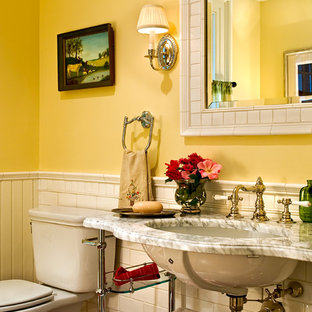 Elegant subway tile powder room photo in New York with marble countertops, an undermount sink, yellow walls and white countertops