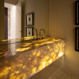 Свежая идея для дизайна: туалет среднего размера в стиле модернизм с фасадами островного типа, бежевыми стенами, полом из известняка, монолитной раковиной, бежевым полом и желтой столешницей - отличное фото интерьера