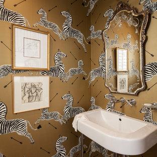 Cette image montre un WC et toilettes traditionnel avec un mur jaune, un sol en bois foncé, un plan vasque et un plan de toilette blanc.
