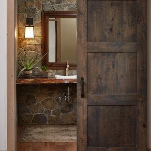 Aménagement d'un WC et toilettes montagne avec une vasque, un plan de toilette en bois, un mur gris, un sol en bois brun et un plan de toilette marron.