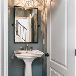 Aménagement d'un petit WC et toilettes campagne avec un mur bleu, un sol en bois foncé, un lavabo de ferme et un sol marron.