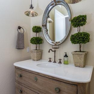 Esempio di un bagno di servizio country di medie dimensioni con consolle stile comò, ante con finitura invecchiata, pavimento in legno massello medio, lavabo sottopiano, top in marmo, pavimento marrone e top bianco