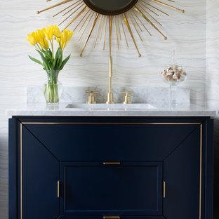 Réalisation d'un WC et toilettes design de taille moyenne avec un placard en trompe-l'oeil, des portes de placard bleues, un carrelage gris, des dalles de pierre, un sol en bois foncé, un lavabo encastré, un plan de toilette en marbre, un sol marron et un plan de toilette blanc.