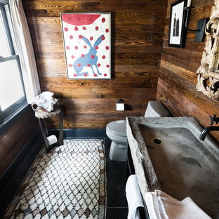 Inspiration for a small rustic cloakroom in Dallas with slate flooring, a trough sink, limestone worktops, black floors, grey worktops, open cabinets, black cabinets, a two-piece toilet and brown walls.