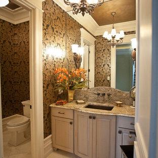 Immagine di un ampio bagno di servizio tradizionale con lavabo sottopiano, ante con bugna sagomata, top in granito, pavimento in marmo, WC a due pezzi e ante con finitura invecchiata