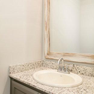 Стильный дизайн: туалет среднего размера в стиле кантри с плоскими фасадами, серыми фасадами, раздельным унитазом, серыми стенами, накладной раковиной, столешницей из гранита, серым полом, белой столешницей и полом из винила - последний тренд