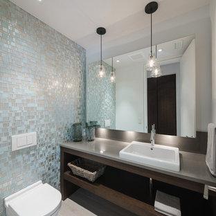 Ispirazione per un bagno di servizio minimal di medie dimensioni con nessun'anta, ante in legno bruno, piastrelle blu, piastrelle grigie e piastrelle di vetro