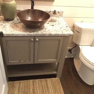 Idee per un piccolo bagno di servizio classico con lavabo a bacinella, top in granito, pavimento marrone, ante a filo, ante grigie e parquet scuro