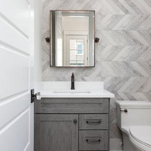 Неиссякаемый источник вдохновения для домашнего уюта: маленький туалет в стиле кантри с плоскими фасадами, серыми фасадами, унитазом-моноблоком, серой плиткой, керамогранитной плиткой, белыми стенами, паркетным полом среднего тона, врезной раковиной, столешницей из искусственного кварца, серым полом и белой столешницей