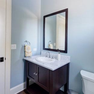 Diseño de aseo clásico renovado con lavabo encastrado, armarios tipo mueble, puertas de armario de madera en tonos medios, encimera de granito y sanitario de dos piezas