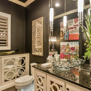 Modelo de aseo romántico con armarios tipo mueble, sanitario de dos piezas, baldosas y/o azulejos negros, paredes negras, suelo de cemento, lavabo sobreencimera, encimera de granito y puertas de armario beige