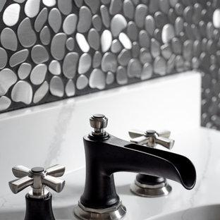 Cette photo montre un WC et toilettes chic de taille moyenne avec un placard avec porte à panneau encastré, des portes de placard noires, un WC suspendu, un carrelage gris, carrelage en métal, un mur gris, un lavabo encastré, un sol marron, un plan de toilette blanc, meuble-lavabo encastré, un plafond voûté et un sol en bois brun.