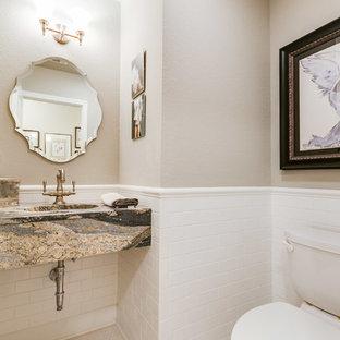 ダラスのトラディショナルスタイルのおしゃれなトイレ・洗面所 (白いタイル、サブウェイタイル、御影石の洗面台、白い床、ベージュの壁、モザイクタイル、一体型シンク、マルチカラーの洗面カウンター、ルーバー扉のキャビネット) の写真