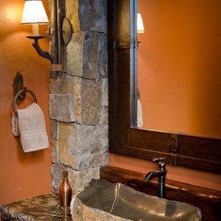 他の地域の大きいラスティックスタイルのおしゃれなトイレ・洗面所 (御影石の洗面台、オレンジの壁、ベッセル式洗面器) の写真