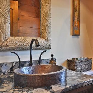 Réalisation d'un petit WC et toilettes chalet avec un placard en trompe-l'oeil, des portes de placard en bois sombre, un WC séparé, un mur beige, une vasque, un plan de toilette en marbre, un sol en bois brun, un sol marron et un plan de toilette noir.