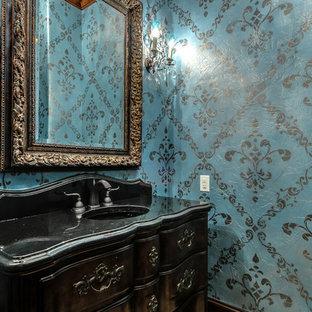 Idées déco pour un WC et toilettes méditerranéen avec un lavabo intégré, des portes de placard en bois sombre, un plan de toilette en granite et un mur bleu.