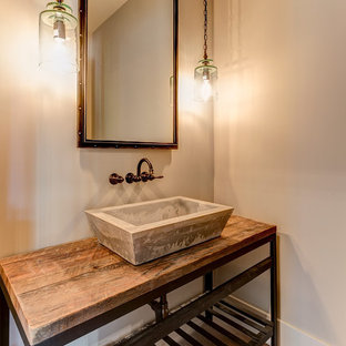 Réalisation d'un WC et toilettes urbain avec un placard en trompe-l'oeil, un mur beige, un sol en bois brun, une vasque, un plan de toilette en bois et un plan de toilette marron.