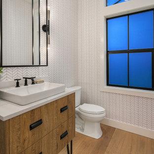 Свежая идея для дизайна: туалет среднего размера в стиле кантри с фасадами островного типа, фасадами цвета дерева среднего тона, раздельным унитазом, белой плиткой, паркетным полом среднего тона, настольной раковиной, бежевым полом и белой столешницей - отличное фото интерьера