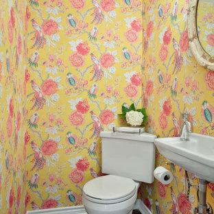 Esempio di un piccolo bagno di servizio con WC a due pezzi, pareti gialle, pavimento in mattoni, lavabo sospeso e pavimento rosso