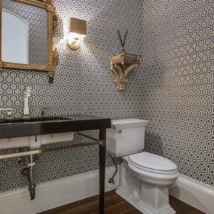 Immagine di un bagno di servizio mediterraneo con lavabo sottopiano, WC a due pezzi, pareti multicolore, parquet scuro e top nero