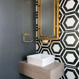 Modelo de aseo actual con paredes multicolor, lavabo sobreencimera, encimera de madera, baldosas y/o azulejos blancas y negros y baldosas y/o azulejos multicolor