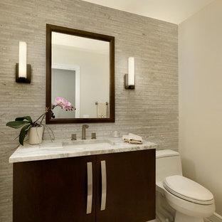 Inspiration pour un WC et toilettes design de taille moyenne avec un placard à porte plane, des portes de placard en bois sombre, un plan de toilette en quartz, un WC à poser, un mur beige, un lavabo encastré et un plan de toilette blanc.
