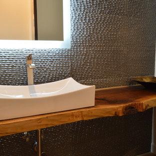 Cette photo montre un petit WC et toilettes éclectique avec une vasque, un plan de toilette en bois, un carrelage gris et un mur gris.