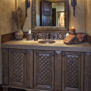 フェニックスの中くらいの地中海スタイルのおしゃれなトイレ・洗面所 (家具調キャビネット、茶色いキャビネット、メタルタイル、ベージュの壁、無垢フローリング、アンダーカウンター洗面器、コンクリートの洗面台、茶色い床、ブラウンの洗面カウンター、一体型トイレ) の写真