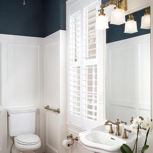 Ejemplo de aseo tradicional con sanitario de dos piezas, paredes multicolor, suelo de madera oscura, lavabo con pedestal y suelo marrón