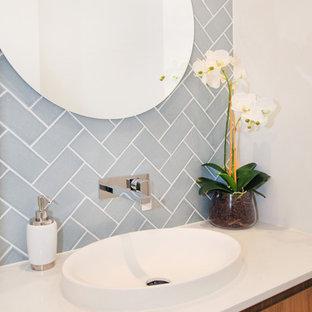 Стильный дизайн: маленький туалет в современном стиле с фасадами островного типа, светлыми деревянными фасадами, унитазом-моноблоком, синей плиткой, керамической плиткой, белыми стенами, полом из керамической плитки, накладной раковиной, столешницей из искусственного кварца, бежевым полом и белой столешницей - последний тренд