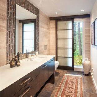 Ejemplo de aseo contemporáneo con lavabo bajoencimera, armarios con paneles lisos, puertas de armario de madera en tonos medios, baldosas y/o azulejos marrones, baldosas y/o azulejos beige y encimeras blancas
