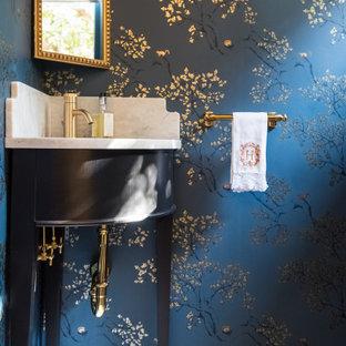 Foto på ett litet vintage vit toalett, med svarta skåp, blå väggar, ett undermonterad handfat och marmorbänkskiva